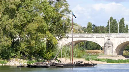 západ : Landscape of Tours, a city in the center-west of France. In the background is the Wilson Bridge. In the foreground, a boat on the Loire.