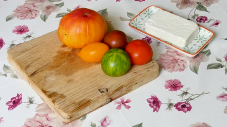 растягивается : In French cuisine, red, orange and green tomatoes are on a cutting board next to a piece of cheese. The whole thing is arranged on a flower cloth. Стоковые видеозаписи