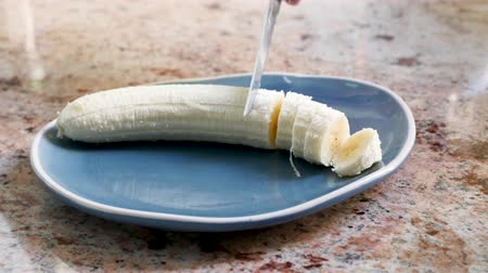 A banana is sliced ??on a plate by someone. The plate is placed on a marble plate in a kitchen.