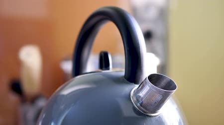 Close-up on a kettle is running in a kitchen. There is smoke, which is water vapor, escaping from it.