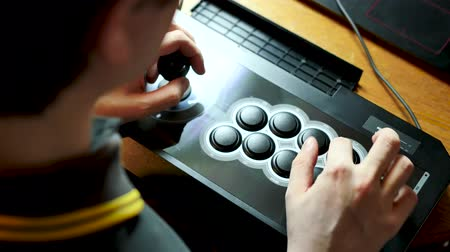A person is playing a video game with an arcade stick. One hand on the joystick and one on the buttons. View from above.