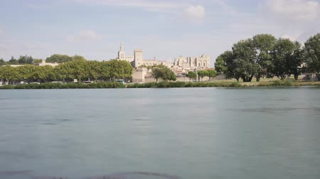 Time lapse in Avignon, an old touristic city in the south of France. In the foreground, there is the Rhone river. In the background, we can see the Papal Palace, a famous historic monument.