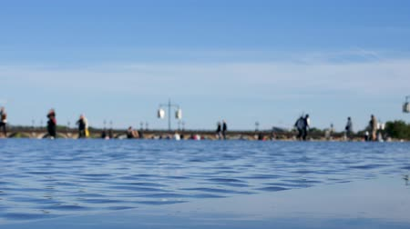 Close-up on the water in the city of Bordeaux, located across from Place de la Bourse. People are walking behind. It is the worlds largest reflecting pool. Blue sky. Filmed in October 2018.