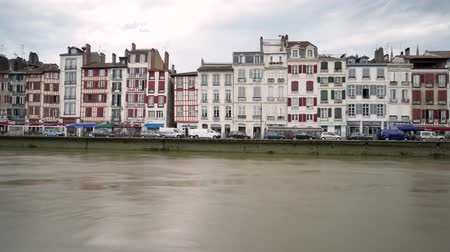 Байон : Time lapse old houses with half-timbered facades in the city of Bayonne. Cloudy weather. View on the banks of the Nive, where there is traffic. Filmed in October 2018.