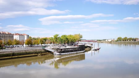 Байон : Time lapse of the banks of the Adour River, in the city of Bayonne, France, near the town hall. It is a city located in the southwest of France. There is a boat moored that reflects in the water. Стоковые видеозаписи