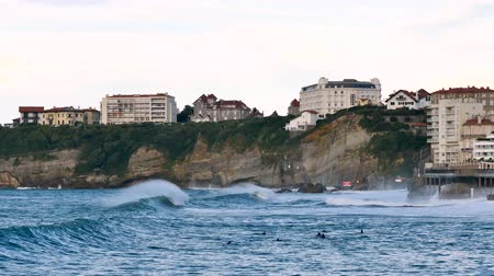 Coast of the city of Biarritz, next to the wide beach. Filmed in October 2018. There are big waves hitting the cliff. Buildings above the cliff. Стоковые видеозаписи