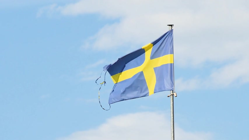 Swedens flag in the wind. Behind, a little cloudy sky.