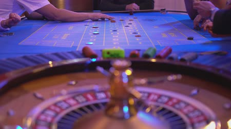 játékpénz : Roulette table in a casino - Gamblers put bets for new game Stock mozgókép