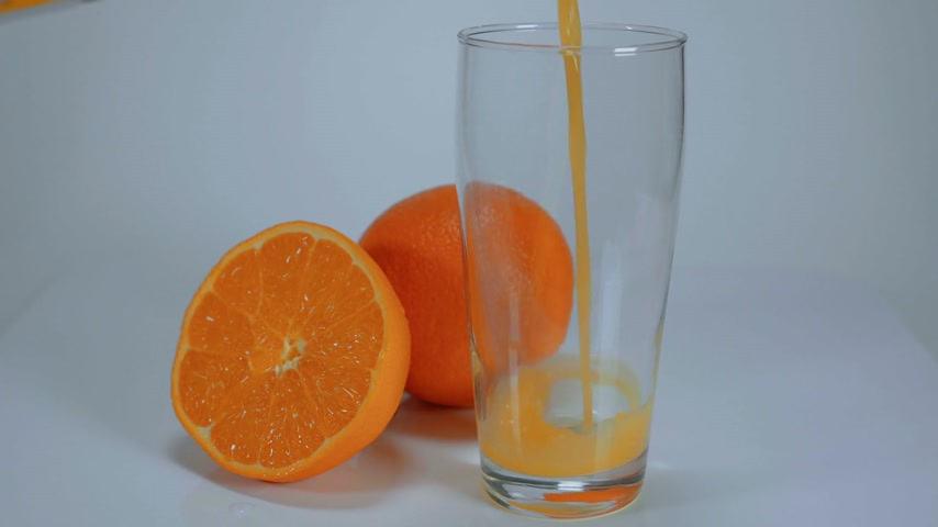 овощи : Pouring freshly squeezed Orange juice in a glass Стоковые видеозаписи