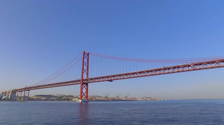 street prhotography : Famous 25th April Bridge over River Tajo in Lisbon aka Salazar Bridge Stock Footage