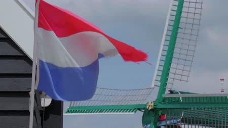 holandês : The flag of the Netherlands in front of a windmill