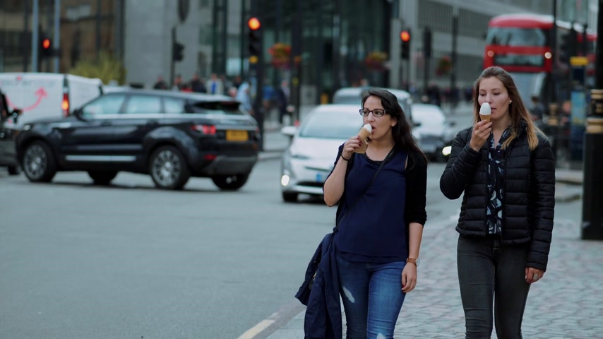 multirracial : Two young women walk through the city of London with ice cream in slow motion - LONDON  ENGLAND - SEPTEMBER 5, 2017