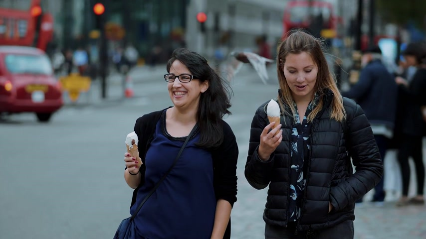 multirracial : Two young women walk through the city of London with ice cream in slow motion Vídeos