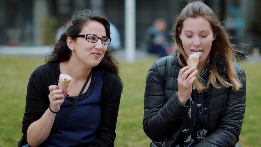multirracial : Two girls sit on the meadows in a park and eat ice cream Vídeos