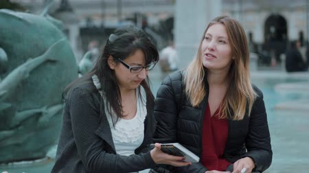 multirracial : Two girls read a travel guide in the city center of London Vídeos
