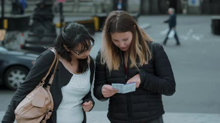 multirracial : Two girls read a map in the streets of London Vídeos