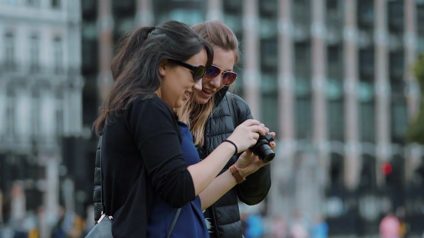multirracial : Two young women check photos on the camera - London sightseeing in slow motion