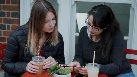 multirracial : Two young women sit in a street cafe and relax