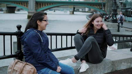 multirracial : Two girls sit at the banks of River Thames and have small talk Vídeos