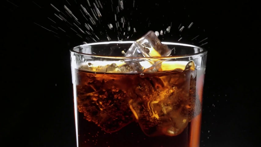 karbonatlı : Ice cubes float in a glass of refreshing cola Stok Video