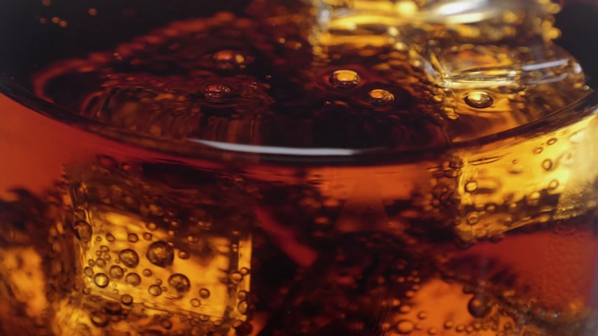 karbonatlı : Close up shot of ice cubes in Cola - refreshing soda in slow motion Stok Video