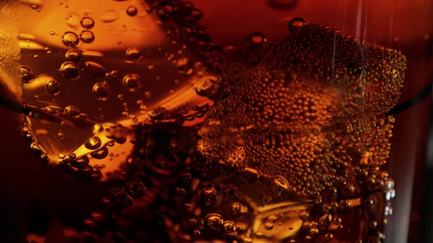 karbonatlı : Slow motion macro shot of ice cubes in a glass of Cola