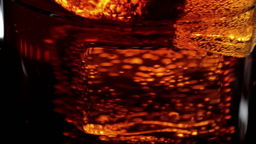 karbonatlı : Marco shot of a glass of refreshing soda - Cola on ice cubes Stok Video