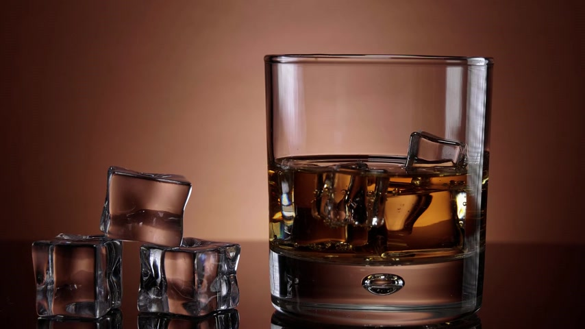 único : A glass of Whiskey on ice - close up shot in slow motion Stock Footage