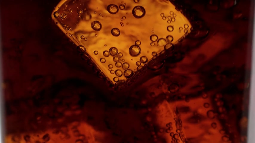 karbonatlı : Close up shot of Cola on ice in slow motion