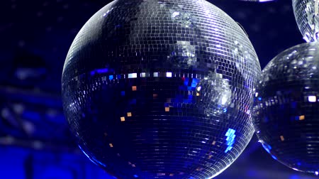 atmosphere : Rotating Mirrorballs in a club reflecting blue light - close up shot