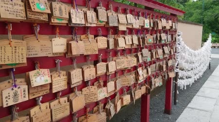 írott : Wishes written on wooden plates in a Buddhist Temple in Japan - TOKYO  JAPAN - JUNE 12, 2018 Stock mozgókép