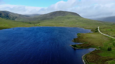 szikla : Beautiful blue lakes in the Highlands of Scotland - aerial drone flight Stock mozgókép
