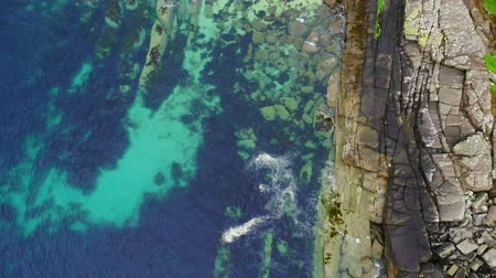 großbritannien : Flight over clear blue ocean water and rocks at the Scottish coastline