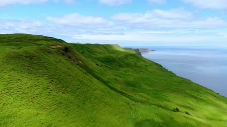 холм : Flight over the green coastline and cliffs on the Isle of Skye in Scotland