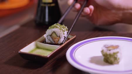 avocado : Dipping sushi rolls into soy sauce
