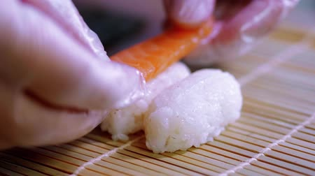 pepino : Preparing Sake nigiri sushi - fresh salmon over rice
