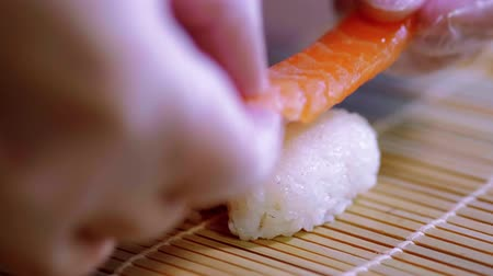 krewetki : Preparing Sake nigiri sushi - fresh salmon over rice