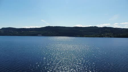 országok : The blue water of Loch Ness - the most famous lake in Scotland - aerial drone flight