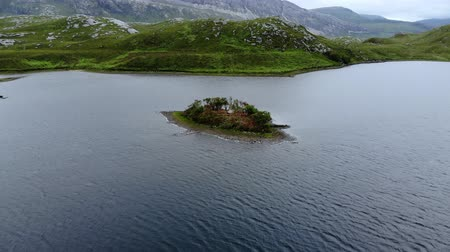 bretanha : Tiny island in the middle of a lake in the Scottish highlands - aerial drone flight
