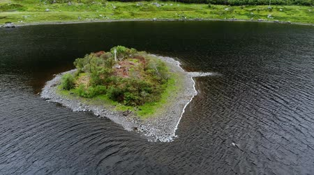 lakes of scotland : Small island in the middle of a lake in the Scottish highlands - aerial drone flight