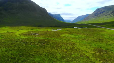 lakes of scotland : Flight over the awesome landscape of Glencoe in the Highlands of Scotland Stock Footage