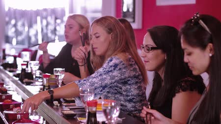 avokado : A group of girls sit in a Sushi Bar restaurant and eat Asian food Stok Video