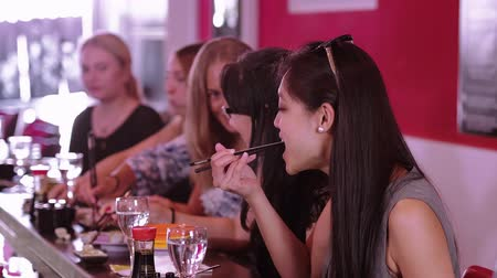 нигири : A group of girls sit in a Sushi Bar restaurant and eat Asian food Стоковые видеозаписи