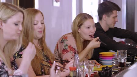 to bite : Young people eat Sushi at a Asian restaurant