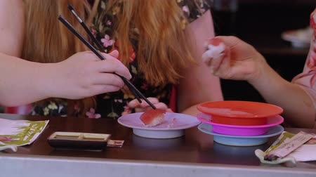 atum : Grabbing Sushi rolls at an Asian restaurant