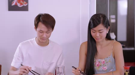 нигири : Young Asian couple in a Sushi restaurant - eating freshly made Sushi rolls