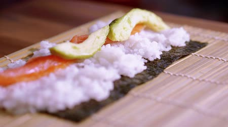 sortimento : Preparing fresh Sushi rolls - close up shot