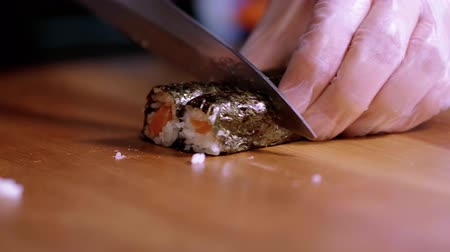 にぎり : Cutting freshly made Sushi rolls into pieces - Asian restaurant