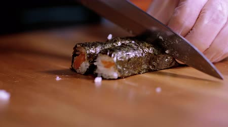 bitkisel : Cutting freshly made Sushi rolls into pieces - Asian restaurant