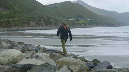 irsko : Girl climbs over the rocks of the Irish coast